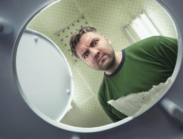 Homme à la recherche dans la cuvette des toilettes