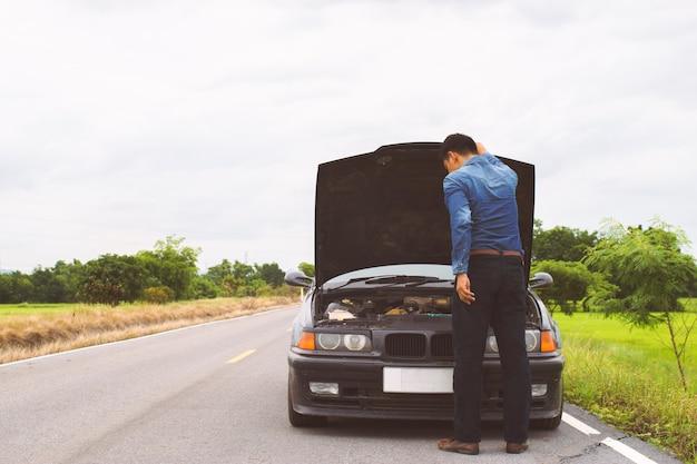 Homme à la recherche de moteur et de système de voiture en panne sur la route.
