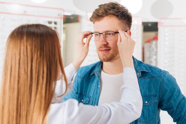 Homme à la recherche de nouvelles lunettes chez l'optométriste