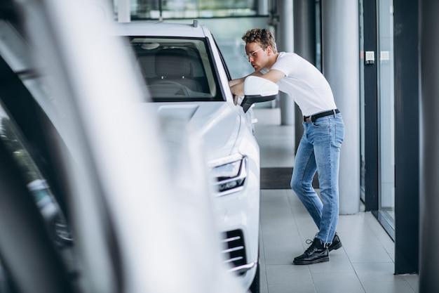 Homme à la recherche d'une voiture dans une salle d'exposition