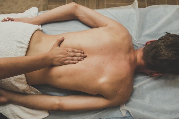 Un homme reçoit un massage du dos. détente sur la table de massage. belle teinte