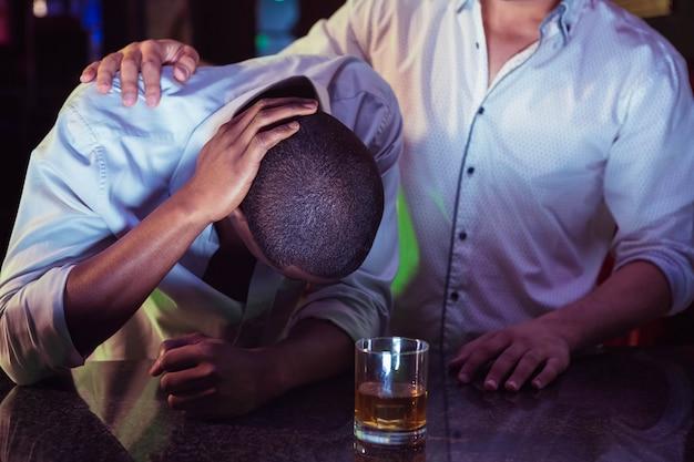 Homme réconfortant son ami déprimé au bar