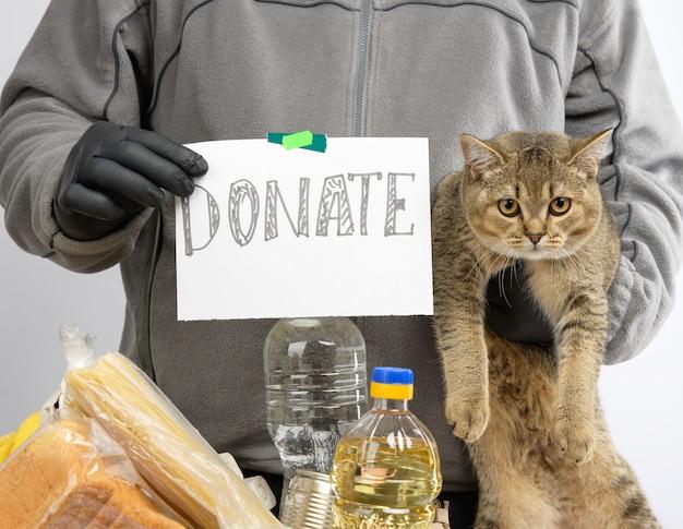 L'homme recueille de la nourriture, des fruits et des choses dans une boîte en carton pour aider les nécessiteux et les pauvres, l'aide et le concept de bénévolat