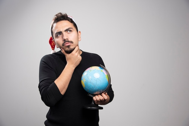 Homme réfléchi au chapeau du père noël posant avec globe.