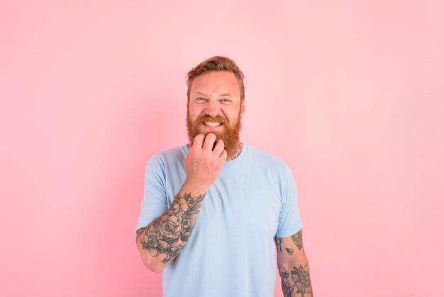 Homme réfléchi avec barbe et t-shirt bleu clair
