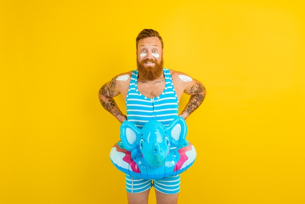Un homme réfléchi avec un beignet gonflable avec un éléphant est prêt à nager
