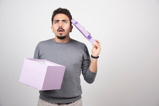 Homme réfléchi avec une boîte violette ouverte sur un mur blanc.