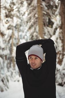 Homme réfléchi, étirant ses mains dans la forêt