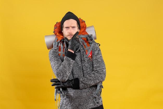 Homme réfléchi avec des gants en cuir et un sac à dos