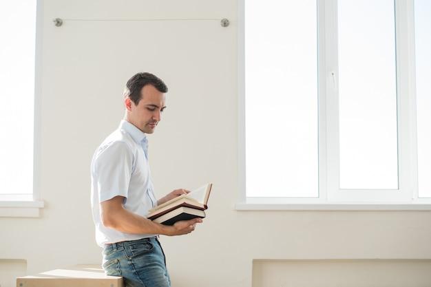 Homme réfléchi qui étudie en classe, lisant un livre