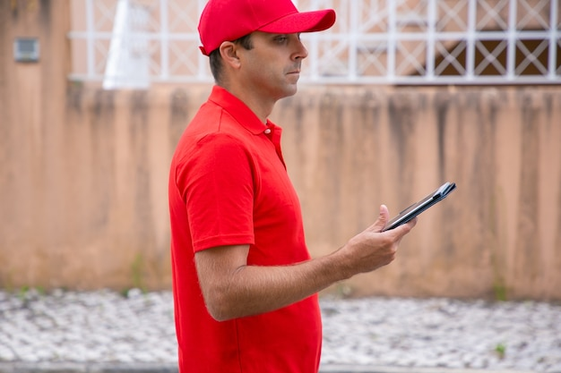 Homme réfléchi tenant la tablette, debout et en détournant les yeux. vue latérale recadrée du courrier caucasien en uniforme rouge à la recherche de l'adresse requise. mise au point sélective. service de livraison et concept de poste