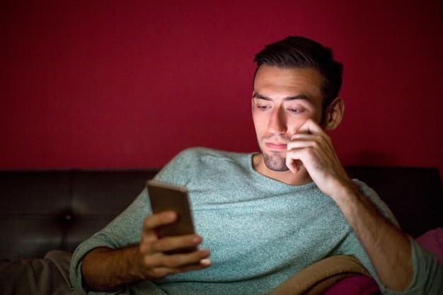 Homme réfléchi utilisant un téléphone intelligent sur le canapé à la nuit