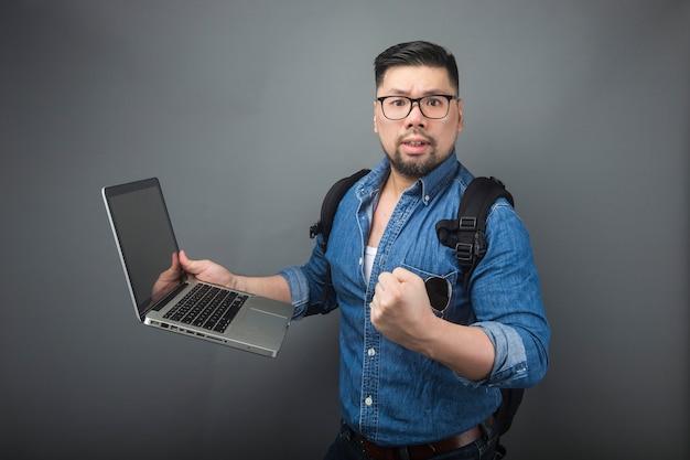 Un homme regarda l'ordinateur avec surprise.
