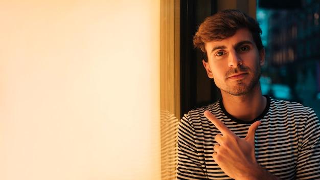 Homme regardant la caméra et pointant son doigt