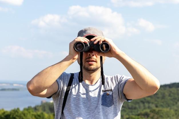 Un homme regardant la caméra à travers des jumelles contre une vue panoramique sur une large rivière sur une colline par une journée ensoleillée