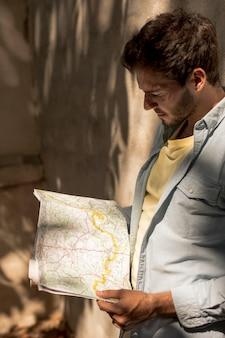 Homme regardant la carte dans l'ombre