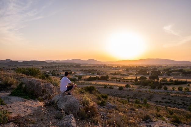 Homme regardant le coucher de soleil dans une montagne
