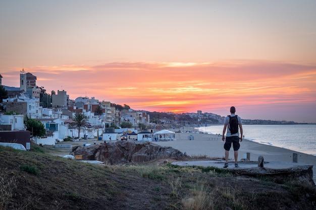 Homme regardant le coucher de soleil sur la plage. village de montgat. (catalogne, espagne)
