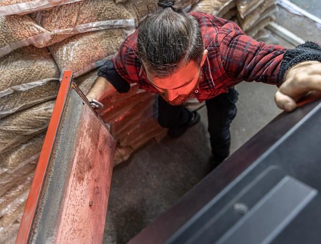 Un homme regardant dans une chaudière sur une chaudière à porte ouverte à combustible solide avec des flammes de feu