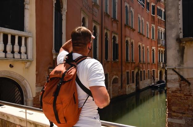 Homme regardant dans les rues en italie, venise, vieilles maisons. rues et canaux de venise. vue sur la rue à venise, italie. homme touristique voyage en italie, venise.