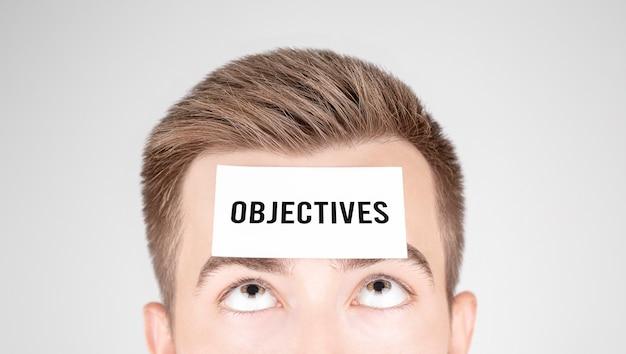 Homme regardant du papier avec des objectifs de mot collé sur son front