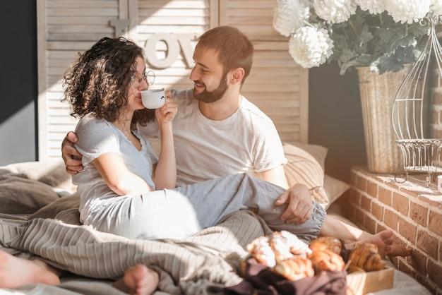 Homme regardant une femme assise sur les genoux d'un homme buvant du café au matin