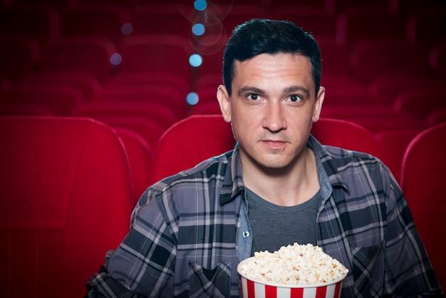 Homme regardant un film au cinéma