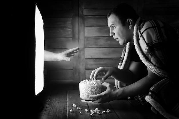 Un homme regardant un film d'horreur à la télévision en noir et blanc