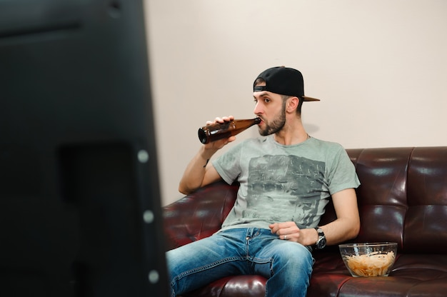 Homme regardant le football et boire de la bière, fan de football