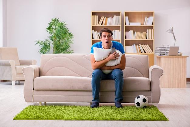 Homme regardant le football à la maison assis sur un canapé