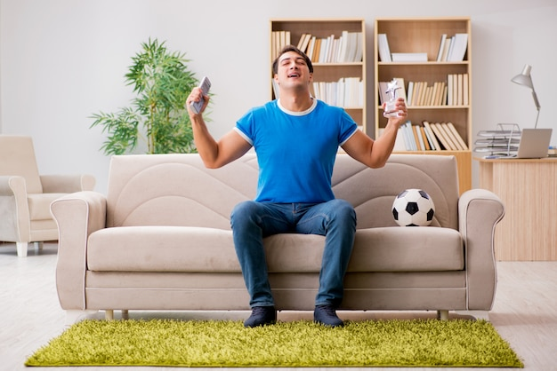 Homme regardant le football à la maison