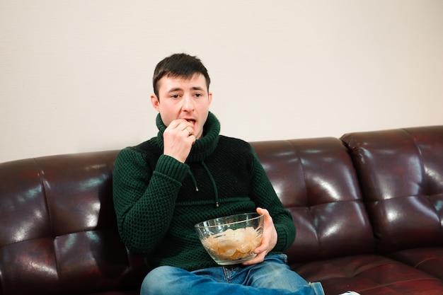 Homme regardant le football et manger des chips, fan de football