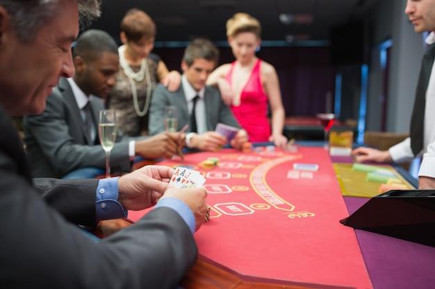 Homme regardant joyeusement à sa main de poker