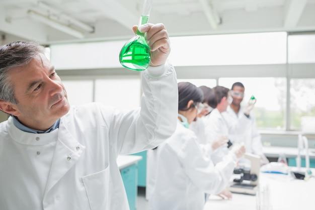 Homme regardant liquide alors que d'autres chimistes font de la recherche