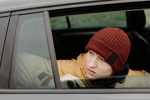 Homme regardant par la fenêtre de la voiture