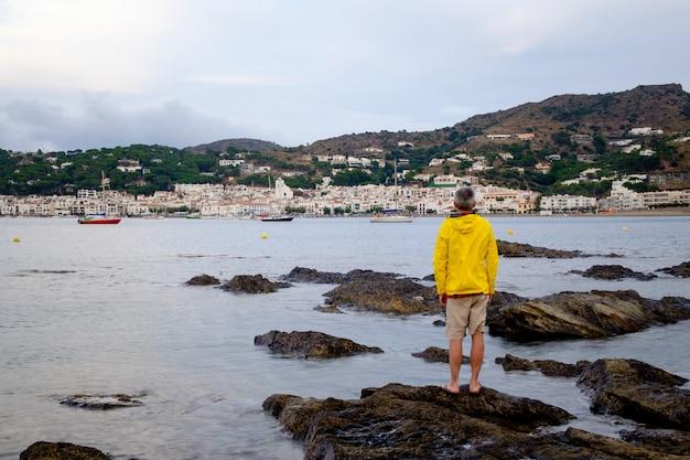 Homme regardant le petit village de port de la selva au coucher du soleil
