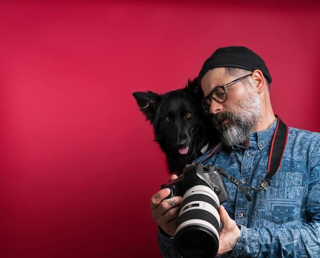 Homme regardant des photos de l'appareil photo avec son chien