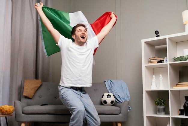 Homme regardant le programme de sport à la télévision