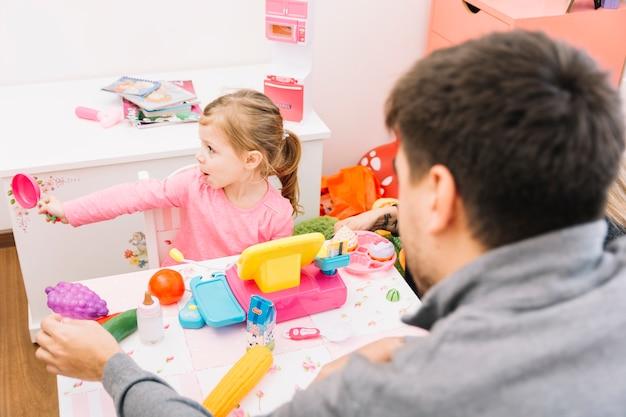 Homme regardant sa fille jouant avec des jouets