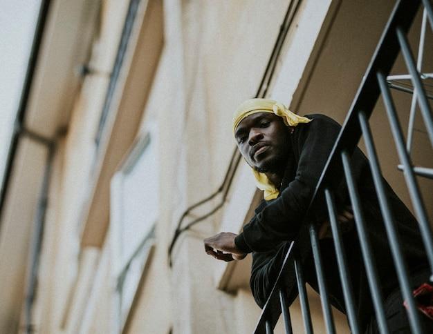 Homme regardant de son balcon pendant l'isolement social en raison de la pandémie de covid-19 en grande-bretagne.