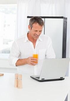 Homme regardant son ordinateur portable pendant qu'il boit du jus d'oranje