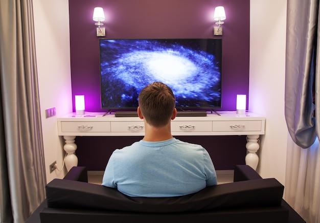 Homme regardant la télévision 4k