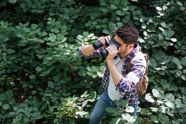 Homme regardant à travers des jumelles en forêt