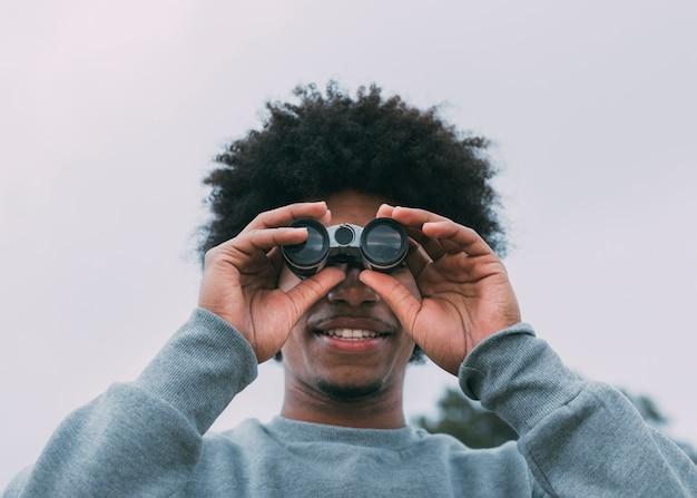 Homme regardant à travers des jumelles