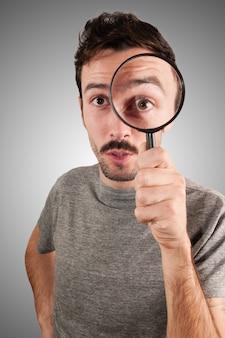 Homme regardant à travers une lentille grossissante