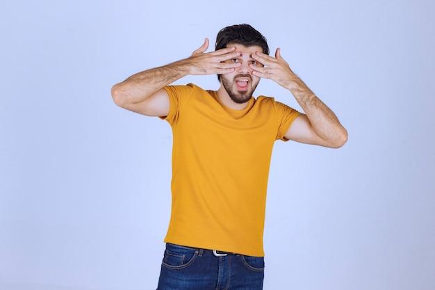 Homme regardant à travers ses doigts