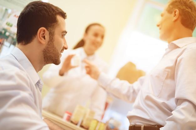 Un homme regarde d'en bas un autre homme qui achète des médicaments.