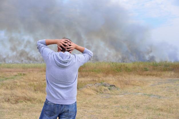 Un homme regarde un champ en feu