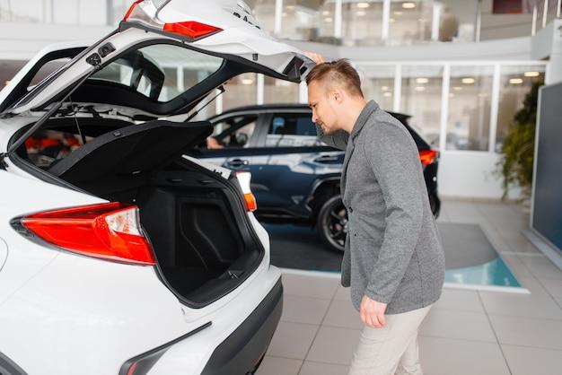 L'homme regarde le coffre de la nouvelle voiture dans la salle d'exposition