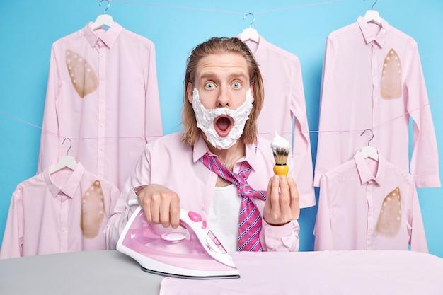 L'homme regarde avec l'expression omg se rase et repasse les vêtements pour le travail ou une occasion spéciale pose sur bleu